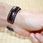 Bracelet jonc en métal gainé de cuir et cousu au point sellier