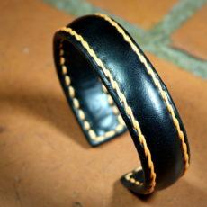 Bracelet jonc en métal gainé de cuir et cousu main
